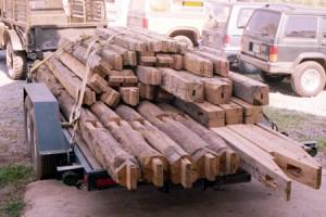 Garage project timber frame elements stacked for transport on trailer.