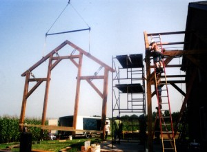 Picked by the crane, a bent for the project is guided into place.