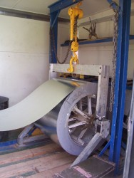 Massive coil of terne metal spooling into the roll former.