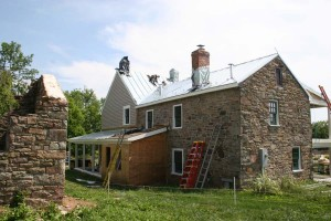The bulk of the roofing has been installed.  The chimneys are temporarily wrapped since the flashings are not complete.  The lower enclosed portion of the side porch is the location of a unique 'cricket' that is especially made to accomodate this lower window.