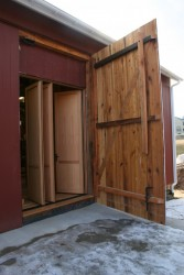 Replicated Heavy-Framed Barn Bridge Doors Hide a Climate-Controlled Entry