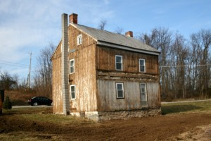 Missing sections of siding indicate that the porch roof was indeed original to the structure, or a very early addition.