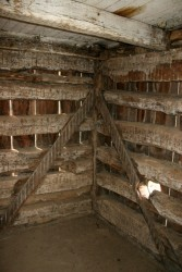 Removing the interior finishes shows that this building was constructed in a very distinctive style where the logs are tenoned into vertical corner posts.