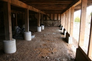 All posts and the forebay wall now rest on tall and wide piers which protect the wood framing from both moisture from animal debris, and impact from livestock and equipment.