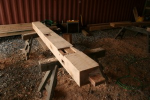 """The design of this building calls for the floor bearing timbers and ties to intersect the posts on the same plane.  That requires heavy bearing shoulders and """"spline"""" joints."""