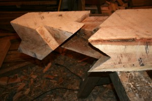 The bottom end is cut to sit on the square and level intersection of two large wall plate timbers.