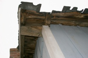 The broken slates are backed up by obviously rotten sheathing boards, and rafters with bad ends.  Significant roof frame damage is very likely.