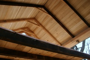 The new loft floor is cut back to open the room space up, and the rough-sawn poplar roof sheathing contrasts nicely against the dark original rafters.