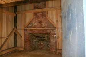 The large cooking hearth, so distinctive of summer kitchens, ready for preparing another meal.