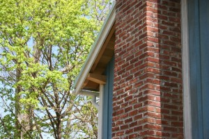 Tapered Plate Timbers pass out through the siding to carry the roof overhangs.