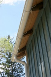 Roof rafters have profiled ends and carry the gutters.