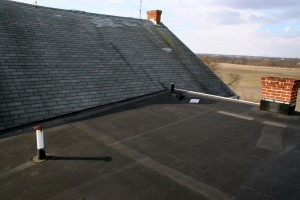 From the opposite side:  Almost flat roof covered in rubber membrane covering portions of two additions.