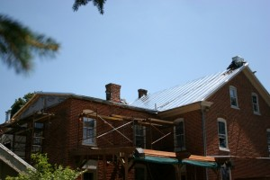 With metal going on, the roofs begin to knit together into a weather-tight assembly.