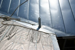 A roofer never wants to see a vent stack coming right out through a valley, but galvanized metal can be soldered very well and we can make this worrisome flashing detail into one solid piece -- as waterproof as a bathtub!