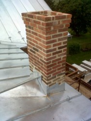 """A """"cricket"""" deflects water and snow from pooling behind a chimney.  We repointed and extended this chimney so it remains sufficiently high above the adjacent new roof."""